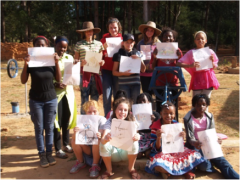 The girls showing off their drawings of water pumps and latrines